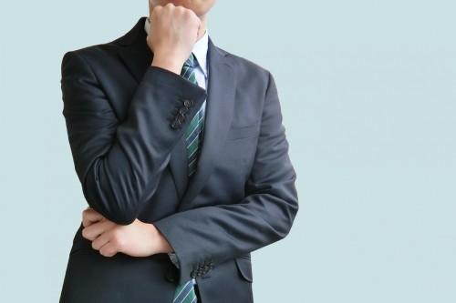 悩むスーツの男性